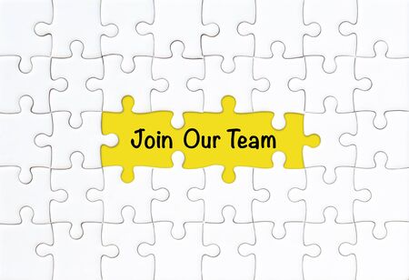 Join our team concept. White jigsaw puzzle with word and yellow background Stock fotó