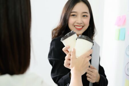 Two beautiful asian business women celebrate their work success by making a clink of a coffee cup, paper cup.