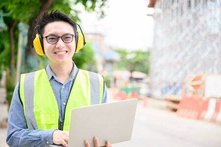Young asian engineers are working on the construction site. Wear a yellow earmuff sound protection and uniform staff. Hand holding computer laptop