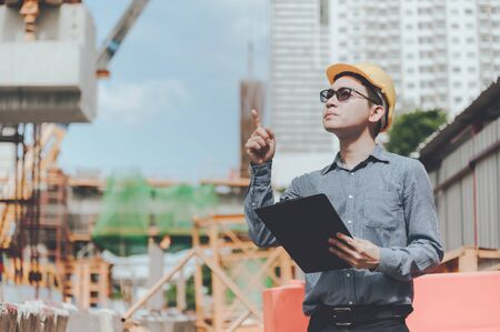 Young asian engineers are working on the construction site and surveying for making contour plans. Wear a yellow helmet safety. Hand holding paperwork document