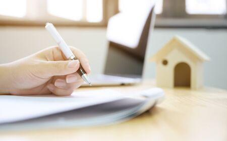 Close up hand of man signing signature loan document to home ownership. Mortgage and real estate property investment Imagens