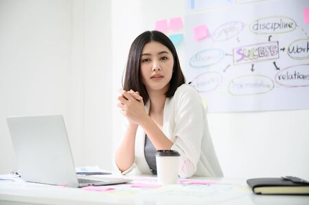 Portrait of beautiful young asian business woman working on computer laptop in office room with paperwork document on desk