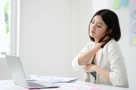Office syndrome concept. Young asian businesswoman feeling pain in neck after working on computer laptop for a long time