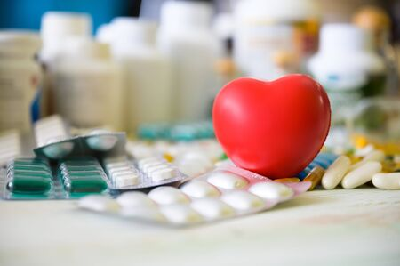 Red heart icon and pill and tablet medicine on wood table. Concept healthcare medical, Insurance for your health