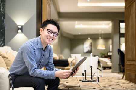 Asian man real estate agent hands holding clipboard document sitting on sofa in example house Stock Photo