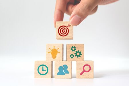 Concept of business strategy and action plan. Hand putting wooden cube block stacking with icon on white background