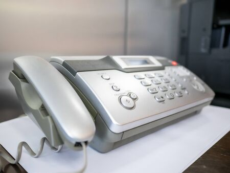 Telephone and fax machine on table in office