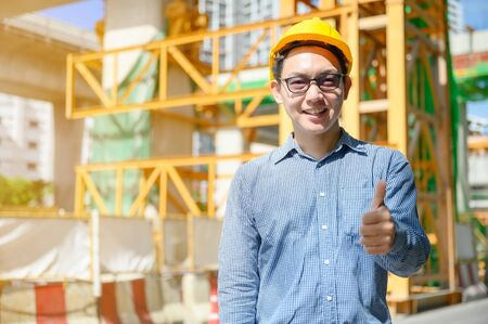 New generation of asian engineers are working on the construction site. He looks handsome and smart.