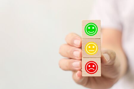Customer service experience and business satisfaction survey. Hand holding wooden block cube with face emotion