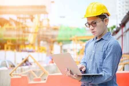 Young asian engineers are working on the construction site. Wear a yellow helmet safety. Hand holding computer laptop