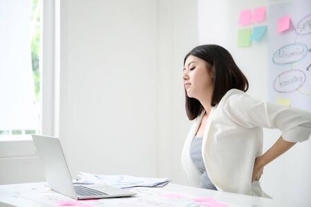 Office syndrome concept. Young asian business woman feeling pain have a backache after working on computer laptop for a long time