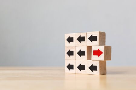 Wooden block with red arrow facing the opposite direction black arrows, Unique, think different, individual and standing out from the crowd concept Stock Photo