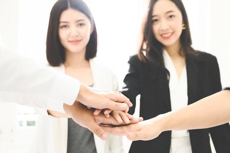 Close up beautiful young businesswoman people putting their hands together. Stack of hands. Unity and teamwork concept.