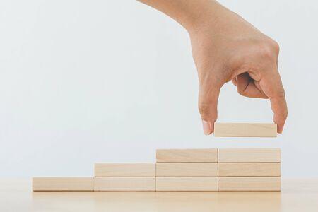 Organiser à la main l'empilement de blocs de bois comme escalier. Concept de cheminement de carrière en échelle pour le processus de réussite de la croissance des entreprises