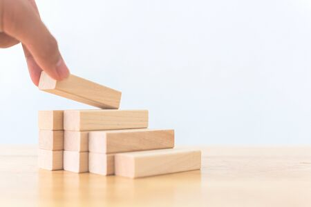 Hand arranging wood block stacking as step stair. Ladder career path concept for business growth success process 写真素材