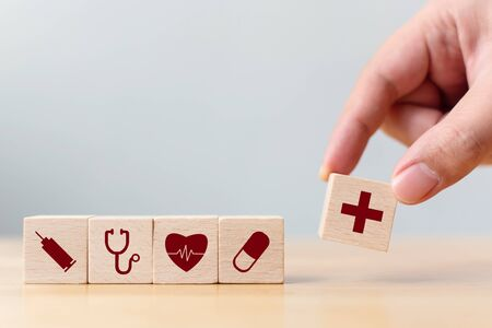 Hand arranging wood block cube shape with icon healthcare medical, Insurance for your health concept 写真素材