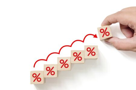 Interest rate financial and mortgage rates concept. Hand putting wood cube block increasing with icon percentage symbol upward direction
