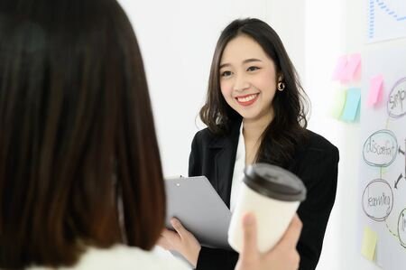 Two beautiful young asian business woman people have fun and talking or discuss about work in workplace