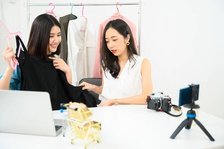Two people young asian female recording video by smartphone for sale product online shopping. Vlogger and blogger concept
