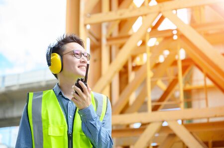Young asian engineers are working on the construction site. Wear a yellow earmuff sound protection and uniform staff. Hand holding portable radio transceiver for communication