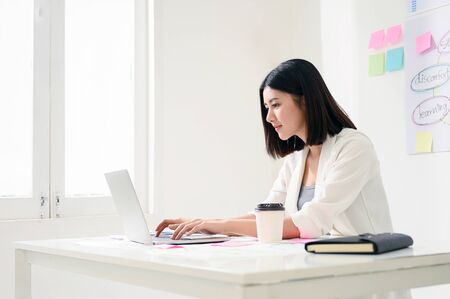 Concept of work from home. Young asian business woman working on computer laptop in office room with paperwork document on desk
