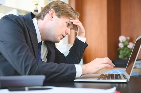 Stressful business man working and laptop on desk in office room