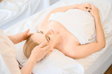Beautiful woman receiving head and facial massage in spa salon. Concept of body health care and traditional thai massage relax Фото со стока