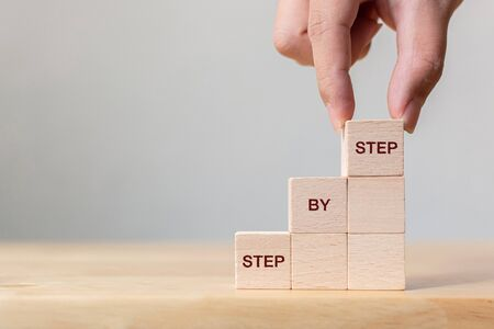 Hand arranging wood block stacking as step stair on top with word Step By Step. Business concept for personal ladder of success process