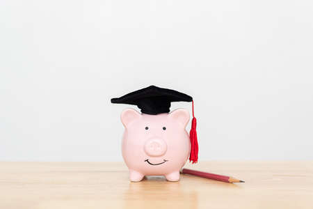 Save money and investment scholarship concept. Piggy bank and pencil on wooden table