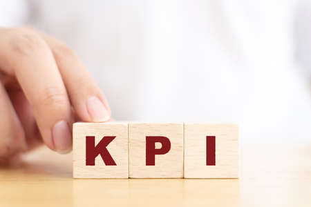 Hand touching wooden cube block with letter KPI is mean key performance indicator Banque d'images