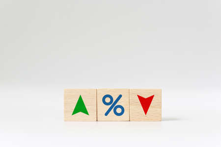 Interest rate financial and mortgage rates concept. Wooden cube block with icon percentage symbol and arrow up and down direction
