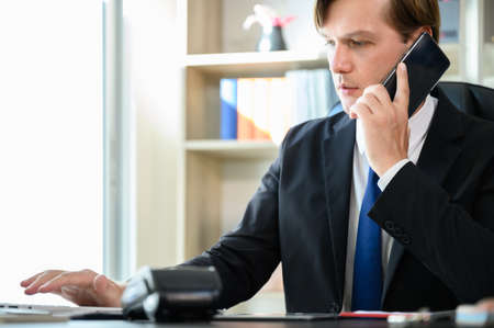 Young business man sitting at his desk working in office room and using smartphone