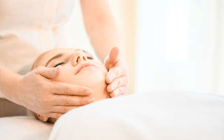 Beautiful woman receiving head and facial massage in spa salon. Concept of body health care and traditional thai massage relax Banque d'images