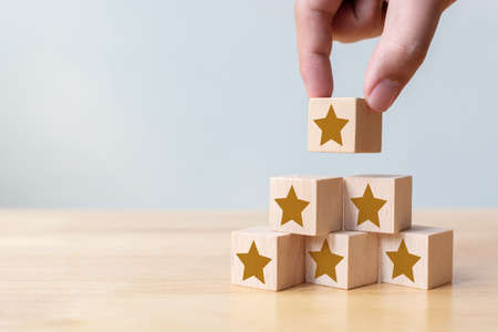Hand arranging wood block stacking as step stair with five star shape. The best excellent business services rating customer experience concept 版權商用圖片