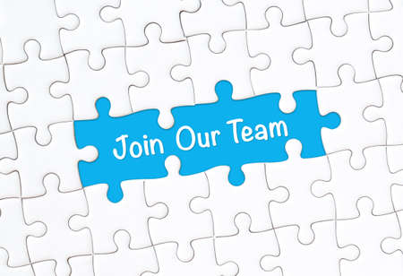 Join our team concept. White jigsaw puzzle with word and blue background