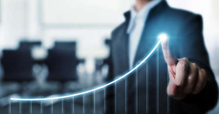 Businessman pointing arrow graph corporate future growth plan with blurred background office. Business development to success and growing growth concept. Stockfoto