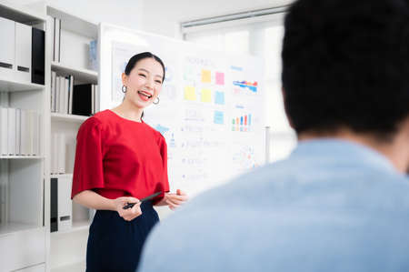 Asian businesswoman report or presentation corporate project to coworker in meeting room. She shows graphics, Pie charts, Diagram and company growth in paperwork document on whiteboard