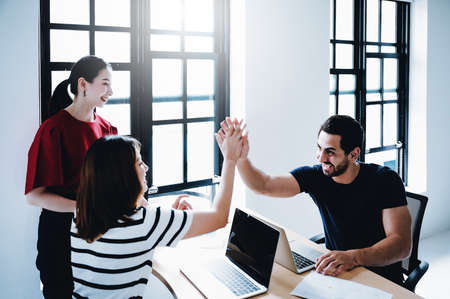 Successful entrepreneurs and business people achieving goals. Happy corporate team giving  high five gesture as they laugh and cheer their succeed, Image motion blur technique Zdjęcie Seryjne