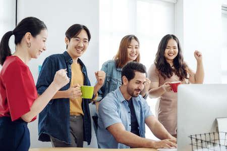 Successful business people group celebrating at meeting in modern office room with desktop computer Zdjęcie Seryjne
