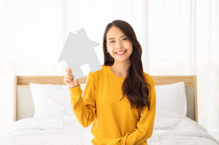 Beautiful asian woman happy and smile sitting on bed in bedroom and holding paper house symbol
