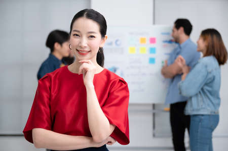Confidence team leader. Young women asian owner startup business looking camera with smile while his colleagues working in the background Zdjęcie Seryjne