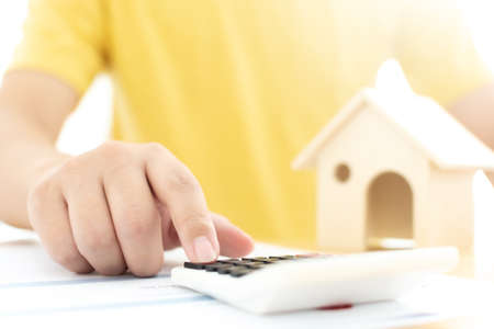 Close up hand of man calculating finance and document home ownership. Mortgage and real estate property managing investment