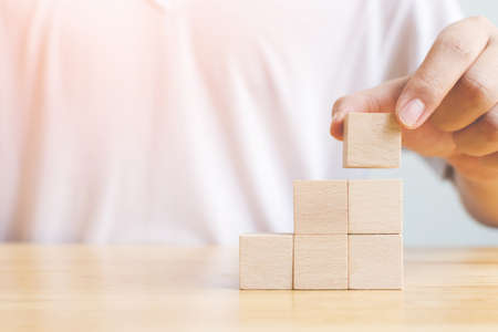 Hand arranging wood block stacking as step stair on top. Business concept for growth success process Stockfoto
