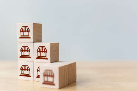 Franchise business marketing system concept. Structure service store network strategy. Wooden block on top with icon store