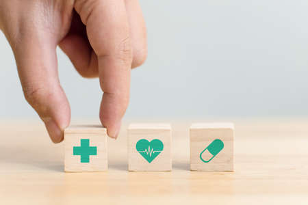 Hand arranging wood block with icon healthcare medical, Insurance for your health concept