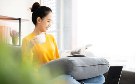 Young asian woman reading a book on sofa and holding a cup coffee in living room