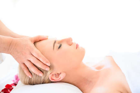 Beautiful woman receiving head and facial massage in spa salon. Concept of body health care and traditional thai massage relax Stockfoto