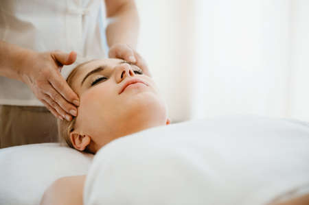 Beautiful woman receiving head and facial massage in spa salon. Concept of body health care and traditional thai massage relax 免版税图像