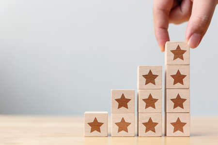 Hand arranging wood block stacking step moving up with icon five star symbol. Rating customer service satisfaction experience concept Stockfoto