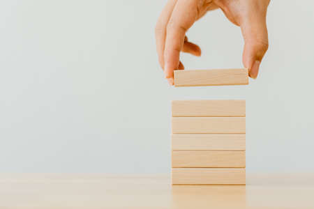 Hand arranging wood block stacking on top with wooden table. Business concept for growth success process Stockfoto